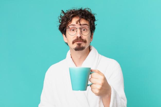 Молодой сумасшедший человек, пьющий кофе