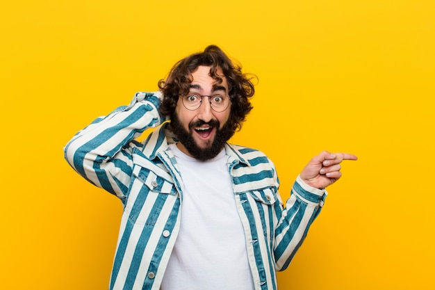 Young crazy man laughing, looking happy, positive and surprised, realizing a great idea pointing to lateral copy space  yellow wall