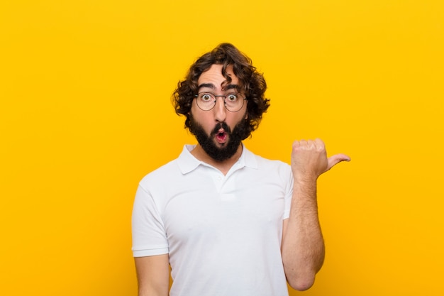 Young crazy man looking astonished in disbelief, pointing at object on the side and saying wow, unbelievable against yellow wall