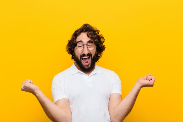 Young crazy man looking extremely happy and surprised, celebrating success, shouting and jumping