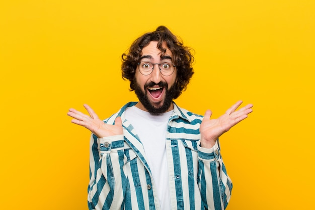 Young crazy man looking happy and excited, shocked with an unexpected surprise with both hands open next to face against yellow wall