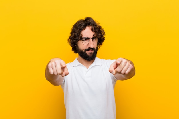 Young crazy man pointing forward at camera with both fingers and angry expression, telling you to do your duty  yellow wall