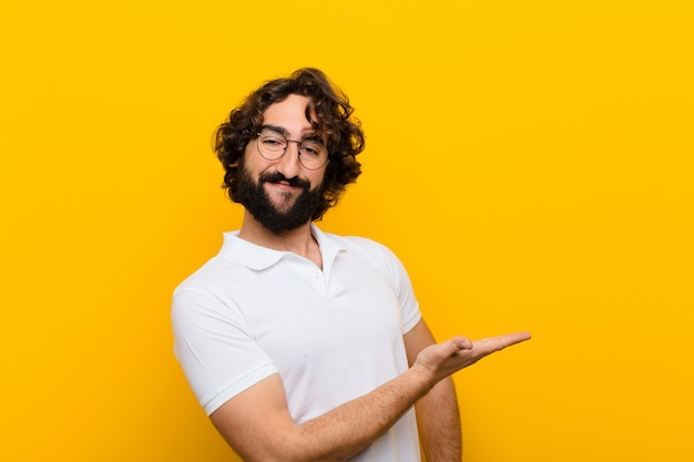 Young crazy man smiling cheerfully, feeling happy and showing a concept in copy space with palm of hand against yellow wall