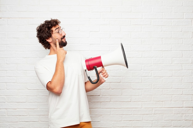 Young crazy man with a megaphone against brick wall.