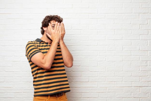 벽돌 벽 배경 감정을 표현하는 젊은 미친 또는 바보 같은 남자