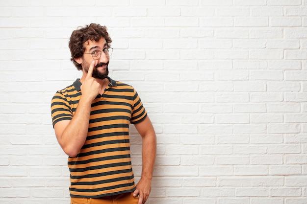 Молодой сумасшедший или глупый человек gesturing и выражение эмоций на фоне кирпичной стены