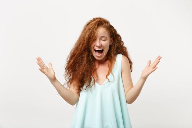 스튜디오의 흰색 벽 배경에 격리된 채 캐주얼한 가벼운 옷을 입은 젊은 미친 빨간 머리 여자. 사람들이 라이프 스타일 개념입니다. 복사 공간을 비웃습니다. 눈을 감고 비명을 지르며 손을 뻗습니다.
