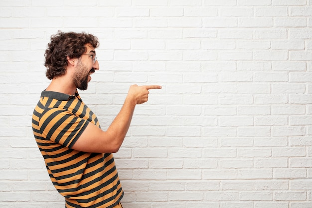 Young crazy or silly man gesturing and expressing emotions against brick wall background