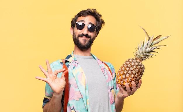 Молодой сумасшедший путешественник счастливым выражением лица и держит ананас