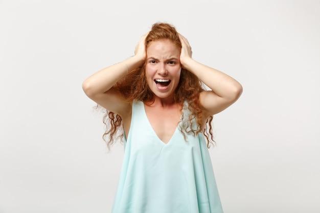 스튜디오에서 흰색 배경에 격리된 채 캐주얼한 가벼운 옷을 입은 젊은 미친 야생 빨간 머리 여성. 사람들은 진심 어린 감정 라이프 스타일 개념입니다. 복사 공간을 비웃습니다. 비명을 지르며 머리에 손을 얹습니다.