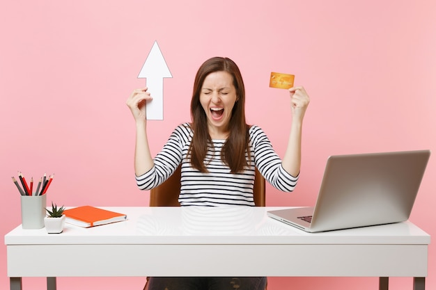 Young crazy winner woman screaming holding up arrow, credit card sit and work at office with contemporary pc laptop isolated on pastel pink background. achievement business career concept. copy space.