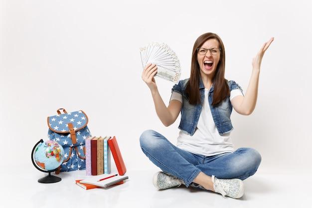 Молодая сумасшедшая студентка кричит, раздвигая руки, держа пачку долларов, наличные деньги сидят возле рюкзака с глобусом, изолированные книги