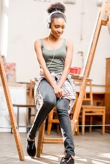 Молодой творческий студент африканской национальности сидит на стуле во время перерыва в университетской студии для рисования