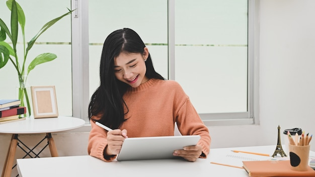 Young creative asian woman using tablet and pen in graphic designer workspace.