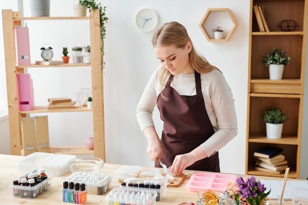 Молодая креативная блондинка в коричневом фартуке рубит мыльную массу на деревянной доске во время работы в студии