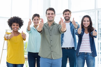 Young creative business people gesturing thumbs up