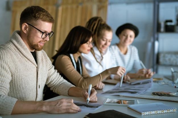 Молодой креативный дизайнер рисует эскиз для новой коллекции моды на фоне консультации коллег