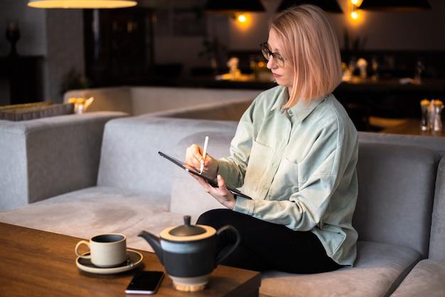 Молодая креативная дизайнерская женщина, держащая стилус, рисунок на цифровом планшете в современном кафе