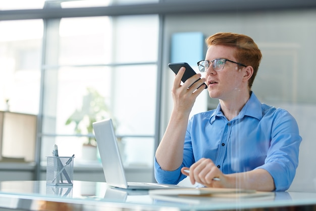 Young creative employee recording voice message while sitting by desk in front of laptop