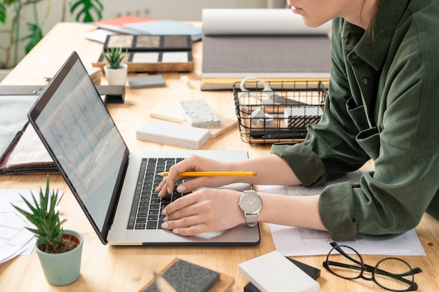 職場で家やアパートの電子スケッチで作業しながらラップトップの前で机の上に曲がる若い創造的な女性デザイナー