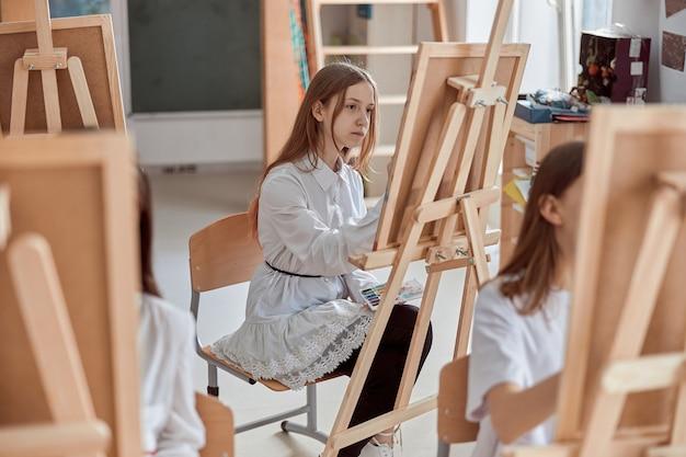 Молодая творческая девушка рисует картину в светлом современном классе
