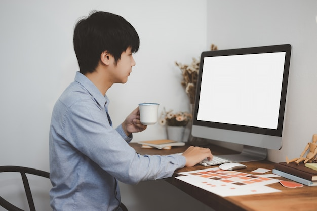 Young creative graphic designer freelancer working with white screen computer mockup at home office.