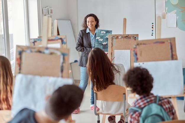 Молодые творческие счастливые ученики в светлом современном классе делают урок рисования