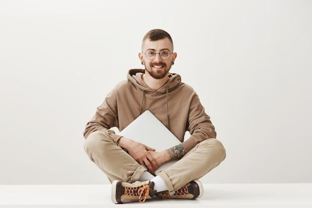 Молодой творческий хипстерский студент сидит со скрещенными ногами и держит ноутбук