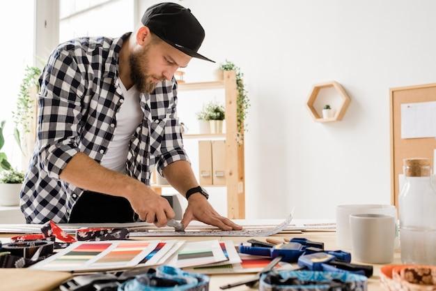 スタジオで装飾的なペットの首輪のワークピースを準備しているときに職場を曲げカジュアルウェアの創造的な若者