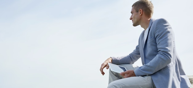 자연에 앉아서 태블릿 컴퓨터를 사용하는 젊은 창조적 인 남자.
