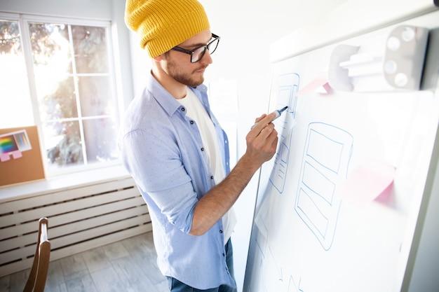Молодой творческий человек записывает идеи на стене, полной липких заметок