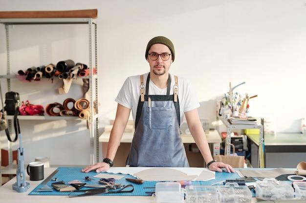 エプロンとビーニー帽子の若い創造的なマスターは、作業用品とテーブルのそばに立っています