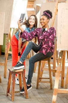 絵画のための大学のスタジオで休憩中に電話で座っている若い創造的な多民族の学生