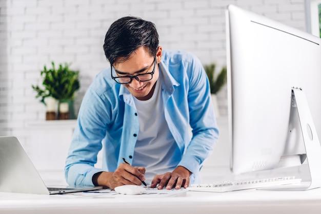 Young creative smiling happy asian man relaxing using desktop computer