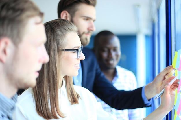 ガラスのポストステッカーで計画やプロジェクトを作成する現代のオフィスで会う若い創造的なスタートアップビジネスの人々