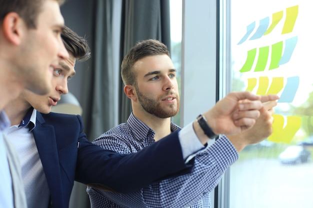 Молодые творческие начинающие деловые люди на встрече в современном офисе, строящие планы и проекты с наклейками на стекле