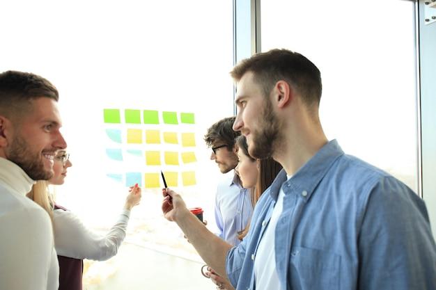 Молодые творческие начинающие деловые люди на встрече в современном офисе, планируют проекты с наклейками на стекле.