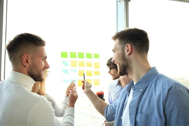 ガラスのポストステッカーで計画プロジェクトを作る現代のオフィスで会う若い創造的なスタートアップビジネスの人々。