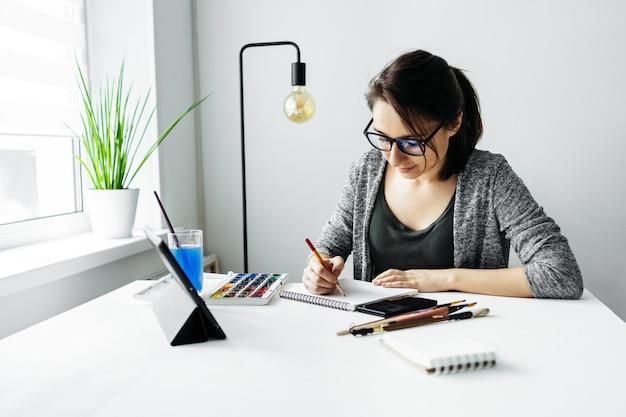 若い創造的な女性アーティストは、水彩絵の具で描きます。タブレット、オンライン学習、美術学校のクラスのコンセプトでビデオコースを見ている女の子。アーティストのライフスタイル。塗装趣味。