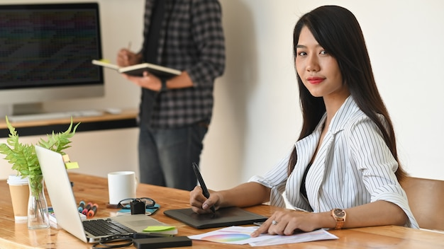 Young creative woman looking at camera on creativity workplace.