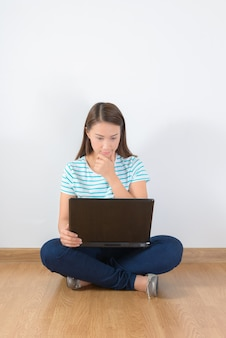 Young creative woman sitting in the floor with laptop