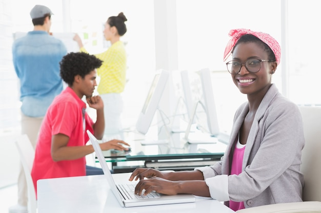 Young creative woman using laptop at desk