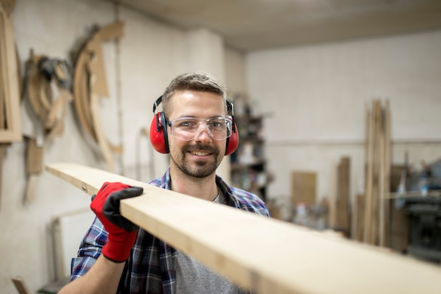 Young creative worker carpenter holding plank wood material in carpentry workshop