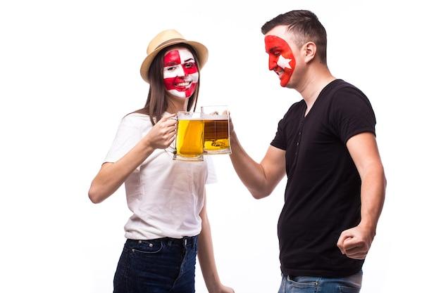 白い壁に分離されたビールと若いクロアチアとチュニジアのサッカーファン