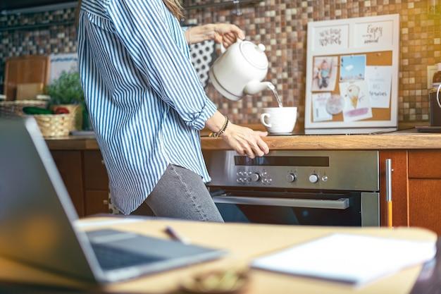 Молодая обрезанная женщина готовит чай за деревянным столом на кухне, наливая воду в чашку из чайника