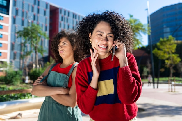 Young crossed arms bored female standing in the street while her woman friend talking on the phone and smiling