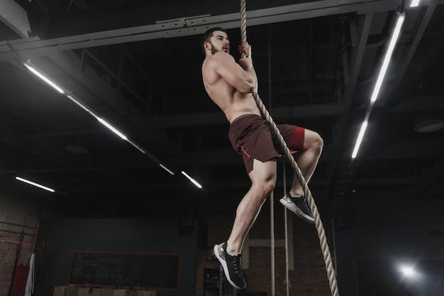 ジムでロープを登る若いクロスフィットアスリート