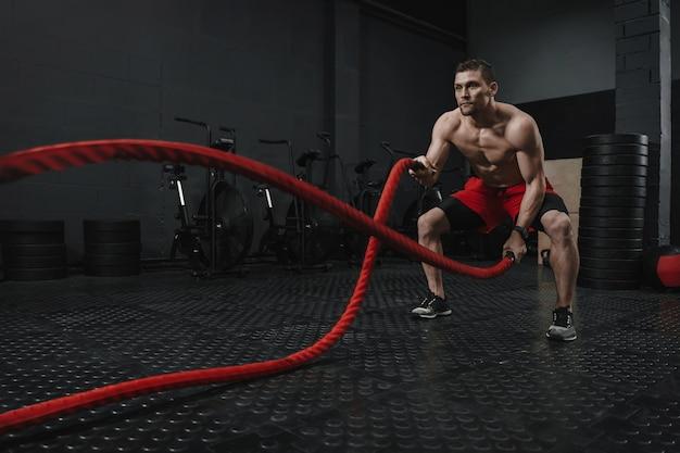 バトルロープをやっている若いクロスフィットアスリートは、フィットネスジムで運動します。ロープでトレーニングをトレーニングする男性。スポーツの動機付けの概念。スペースをコピーします。