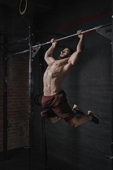 ジムで懸垂をしている若いクロスフィットアスリート。ファンクショナルトレーニングをしているハンサムな男。体操の練習。