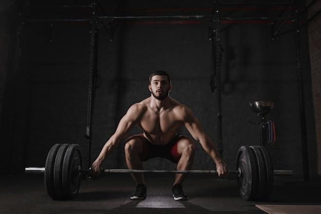 ジムでバーベルを持ち上げる若い crossfit 選手。筋肉の上半身裸の男